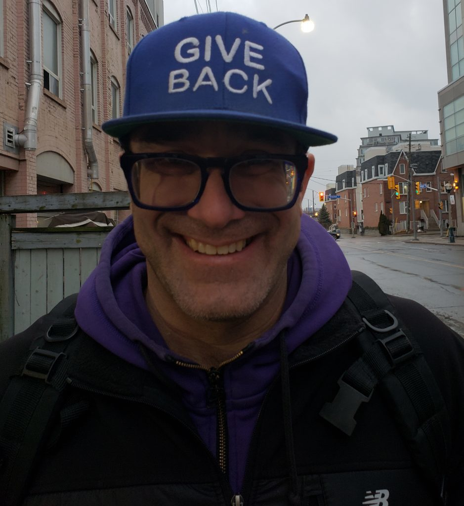 """Jagger Long smiles while wearing a purple hat that says """"give back""""."""