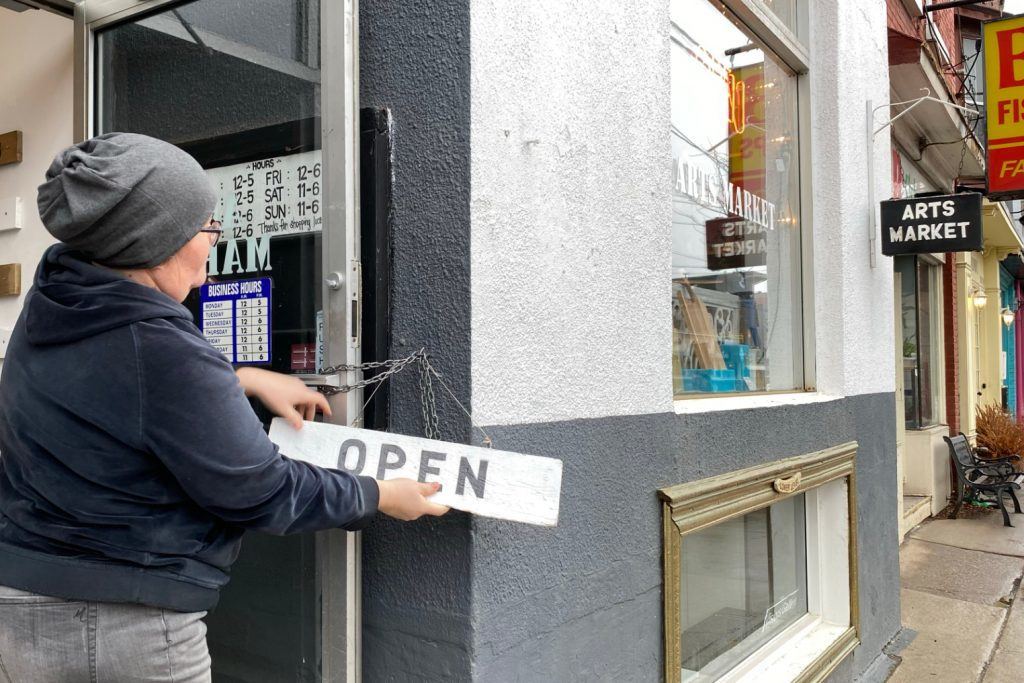 Lindsay Ellis puts an open sign on the store door
