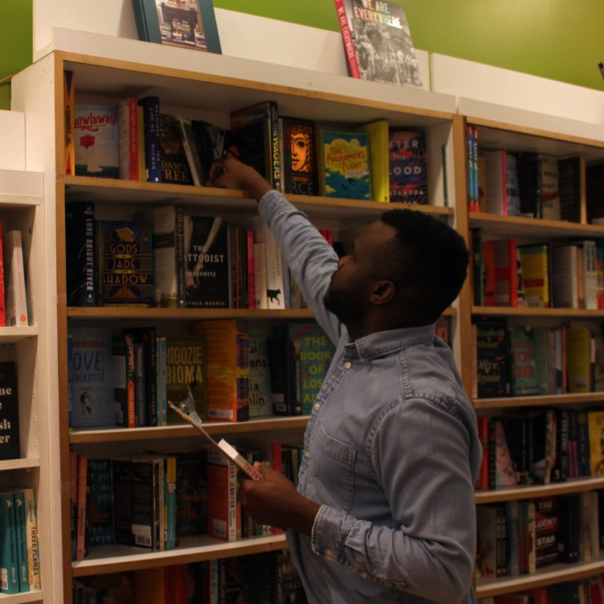 Khary Mathurin standing in front of a bookshelf reaching for a novel on the top shelf.