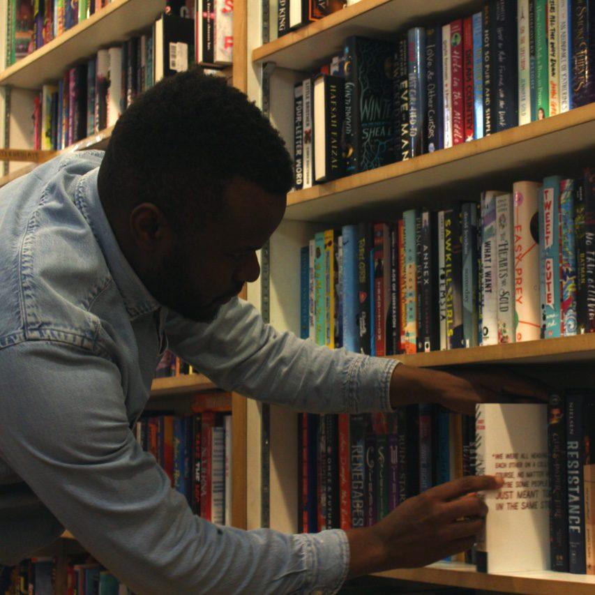 Khary Mathurin taking a novel off the shelf.