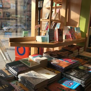 Table by the window of the bookshop holding various books.