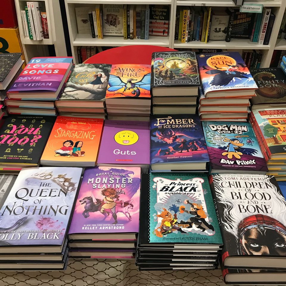 A table top covered with various fiction novels.