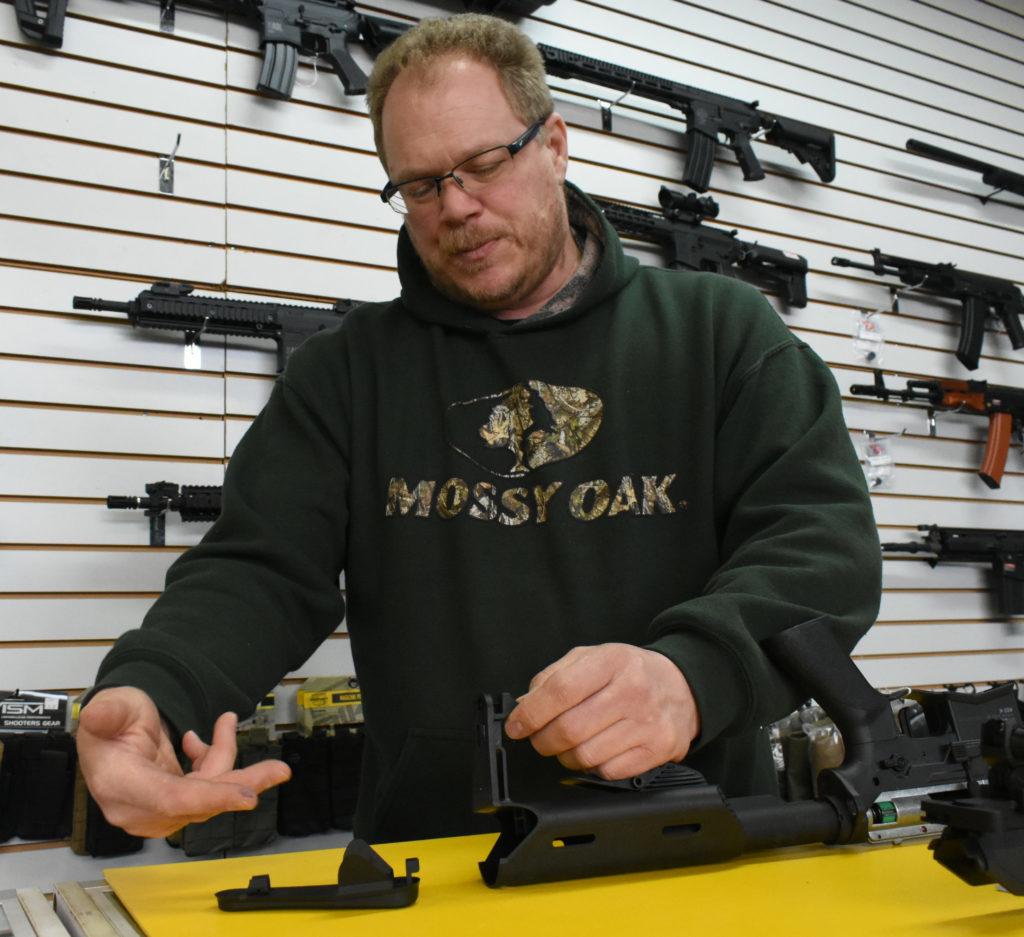 A man putting a cover on a hollow gun buttstock.