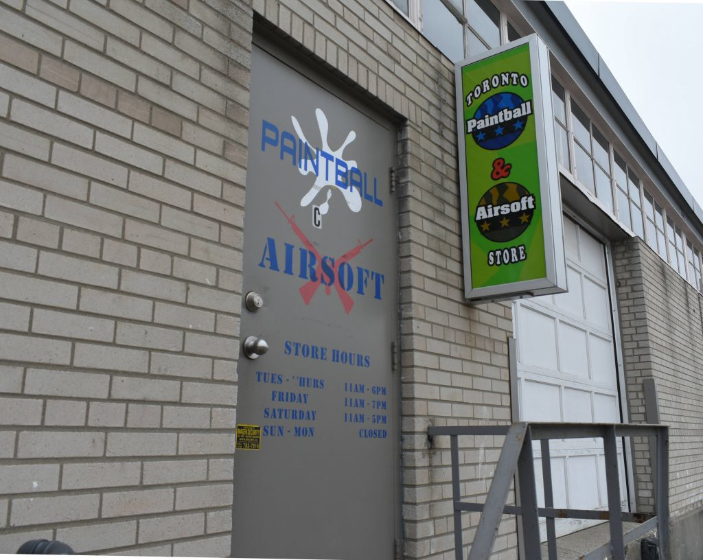 """A door with """"Paintball (&) Airsoft"""", next to a sign saying 'Toronto Paintball & Airsoft Store.'"""