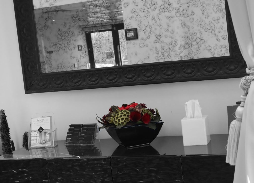 vase with red flowers and mirror upon entry at the New Haven Funeral Centre