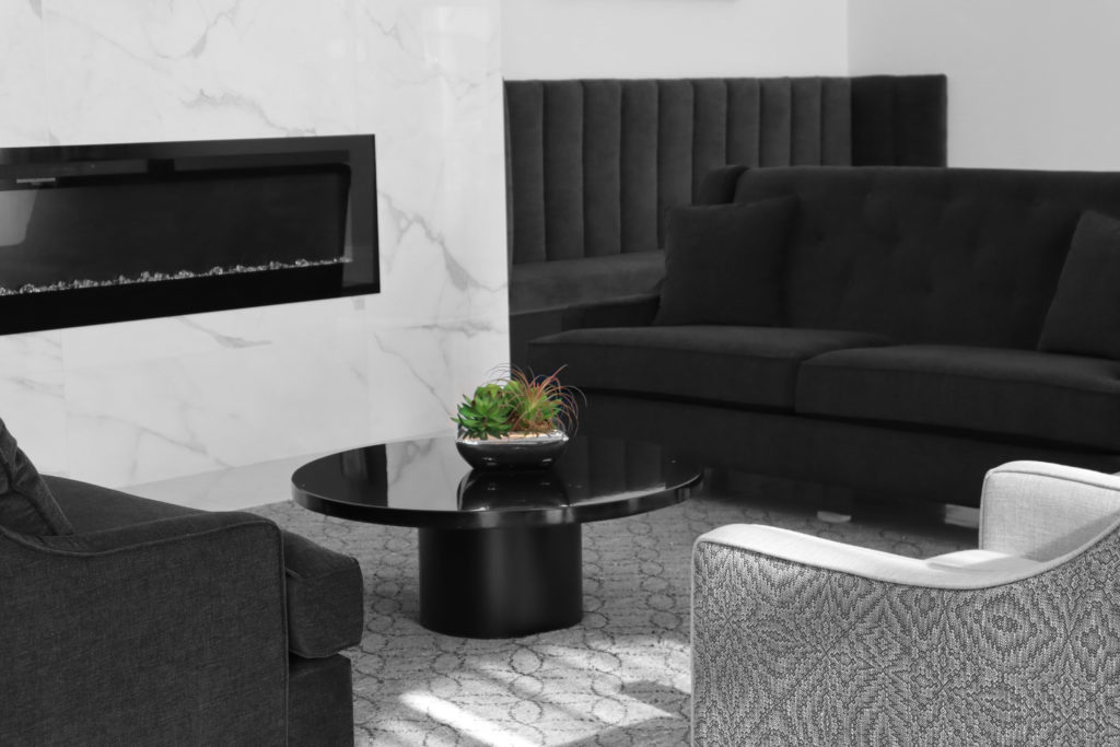 a green plant sits in the middle of three couches and a fireplace at the New Haven Funeral Centre