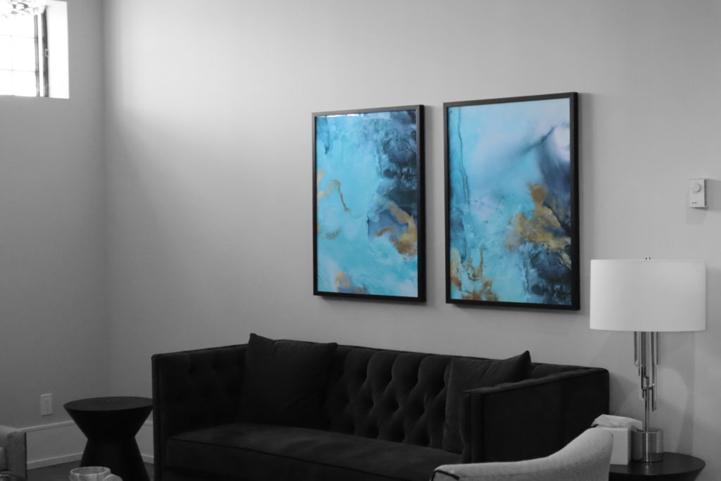 a painting hangs over the top of a couch in the guest suites at the funeral centre