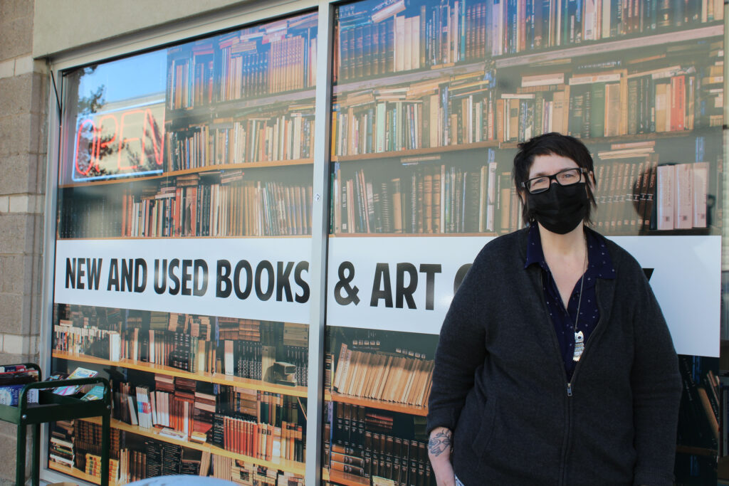 """Woman stands outside with sign reading """"new and used books and art"""" behind her."""