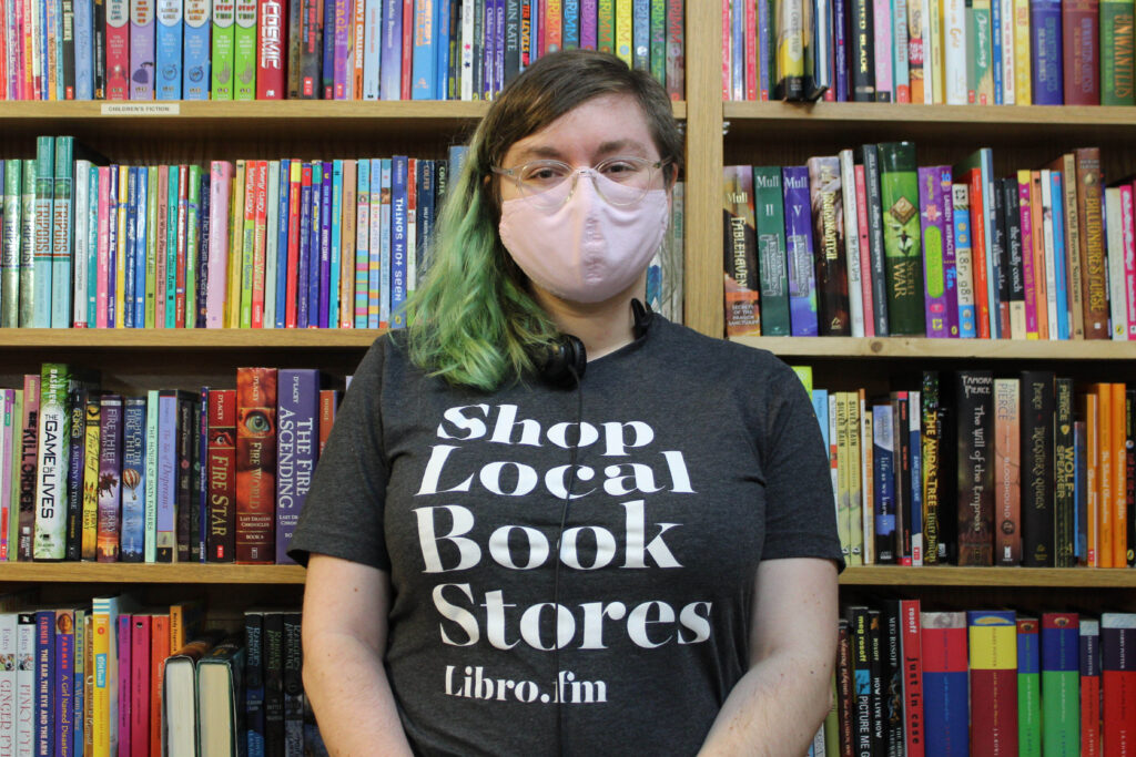 """A woman wearing a """"shop local book stores"""" shirt stands in front of a full bookshelf."""