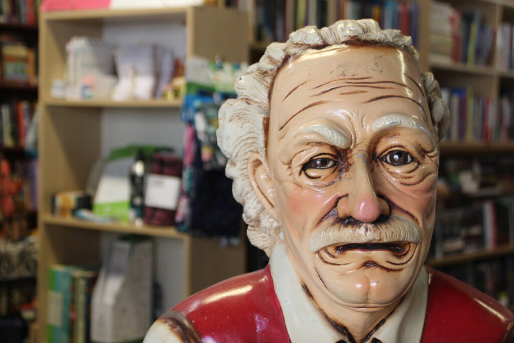Close-up photo of the face of the old man statue. His face is wrinkled and some paint is chipping off.