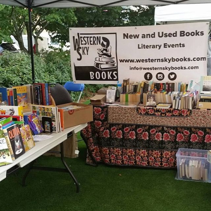 Tables filled with books sit on green grass with a banner for Western Sky Books hanging from the top of a tent.