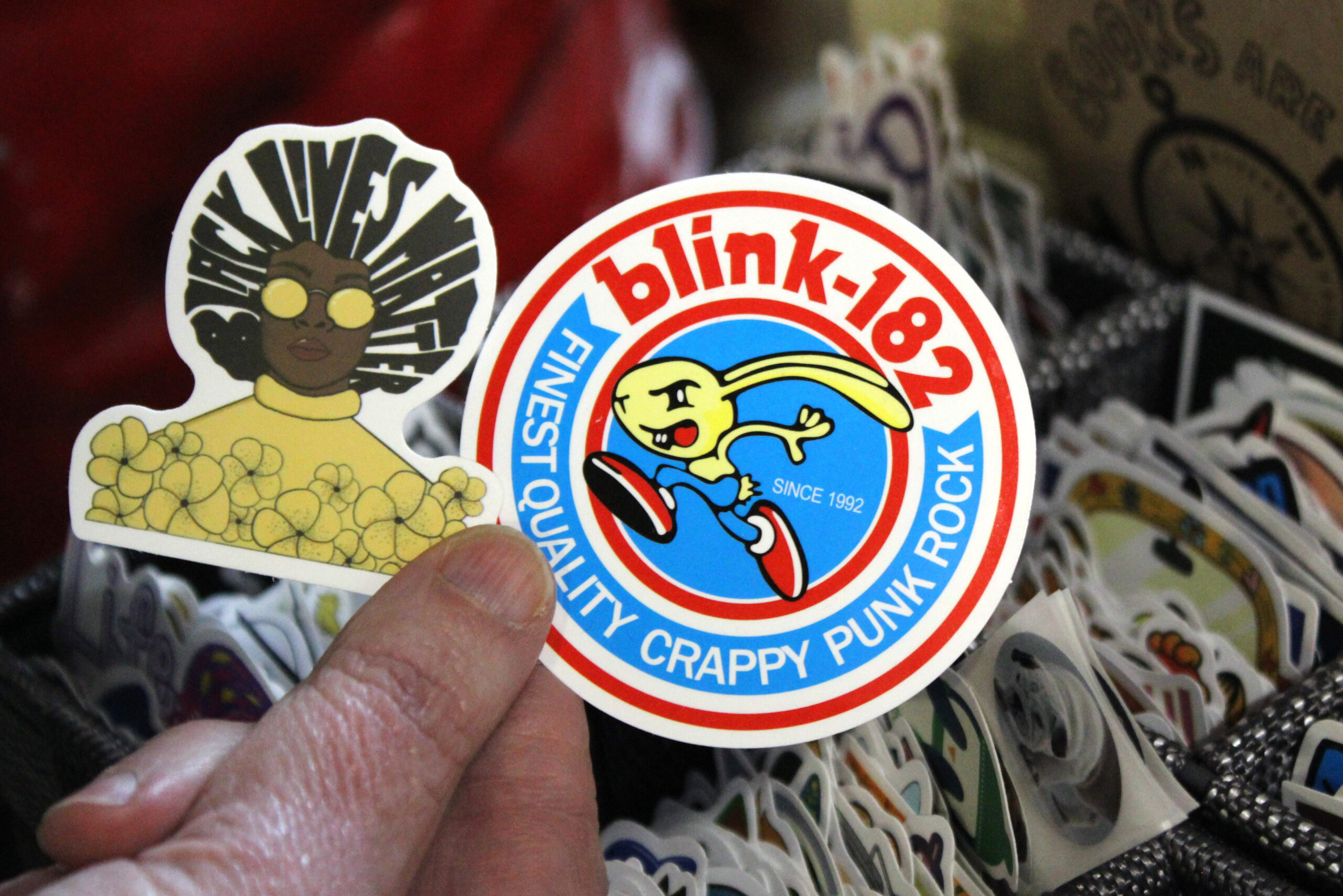 A hand holds two stickers: one with a Black Lives Matter design and the other a Blink-182 design.