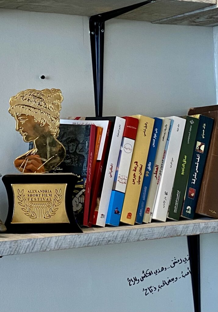 """The Hypatia Golden Award placed beside books, It says on the awad, """"Alexandria Short Film Festival."""""""