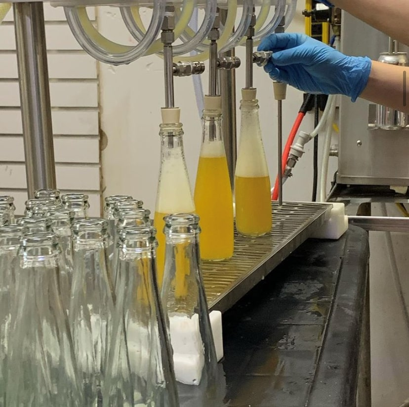 Multiple glass bottles are being filled with soda by a machine. Canalside Soda is filling one-serving bottles at their production facility in Grimsby, Ont.