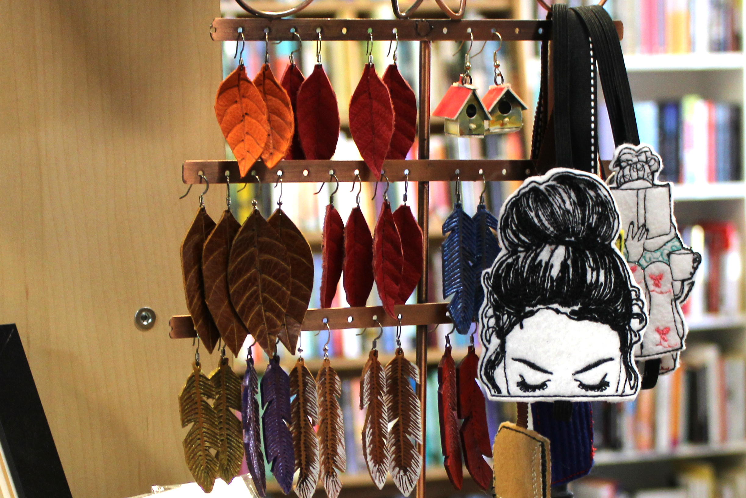Jewelry tree displaying feather-shaped leather earrings. A bookmark of a girl reading dangles off the side.