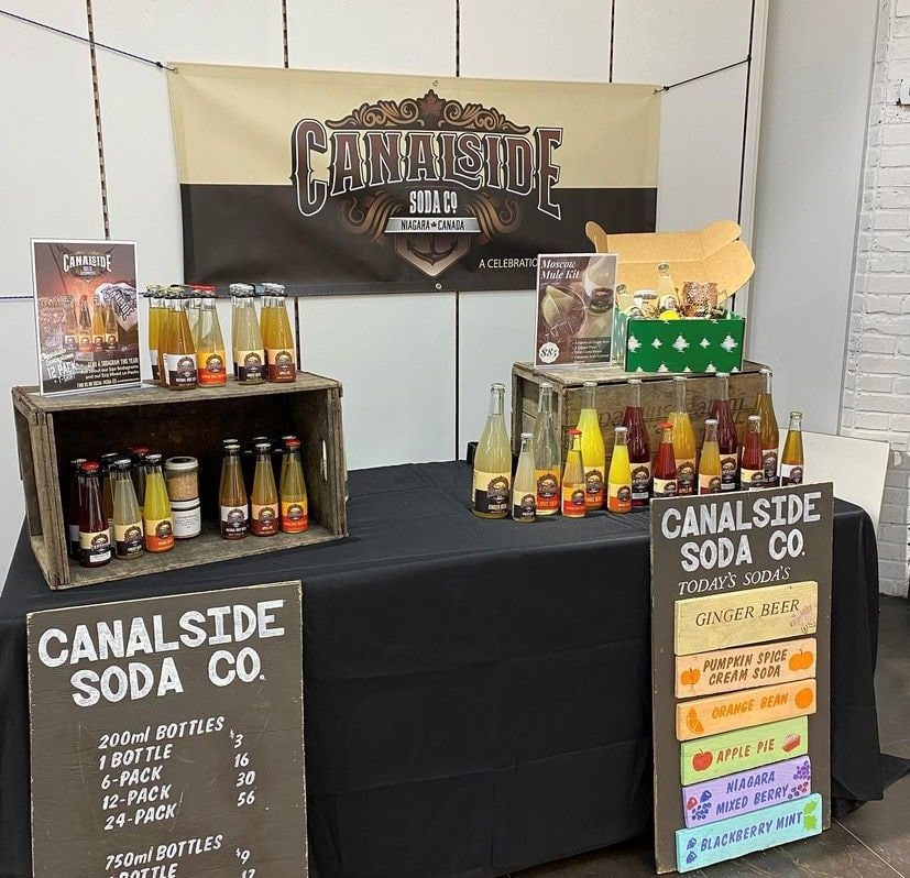 A table with Canalside Soda soda beverages scattered around, with two signs with prices leaning on the ground. Canalside Soda was selling their beverages at the Pen Centre in St. Catharines, Ont.