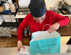 A staff member placing the takeout box in a blue paper bag.