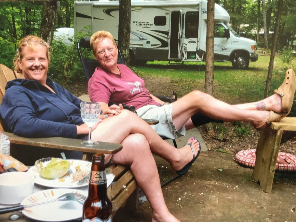 Lori Pilatzke and Jen Maklin sit in Muskoka chairs on a campsite, their RV visible in the background.