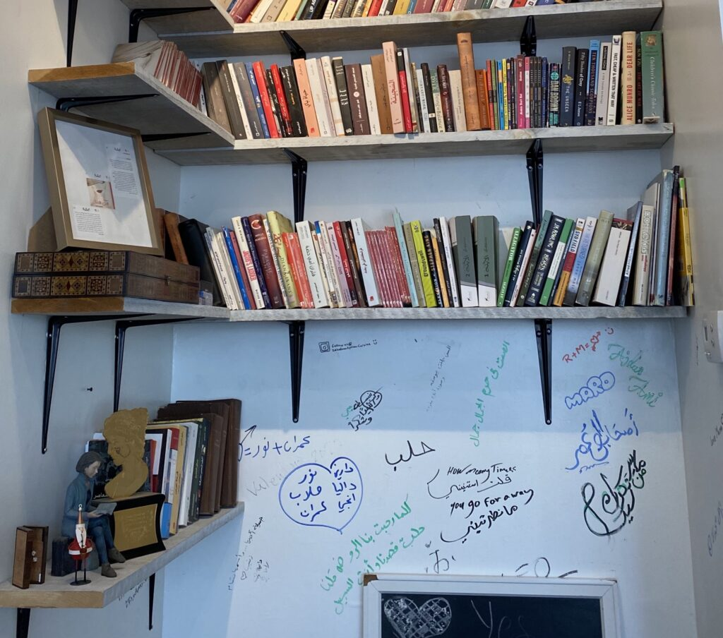 Books placed on shelves above a wall filled with signatures and writings.