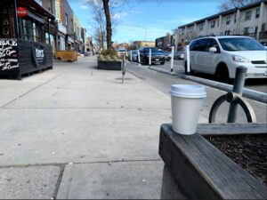 A blank coffee cup sits on the right on an elevated platform. Behind it is an empty sidewalk on Danforth Avenue.