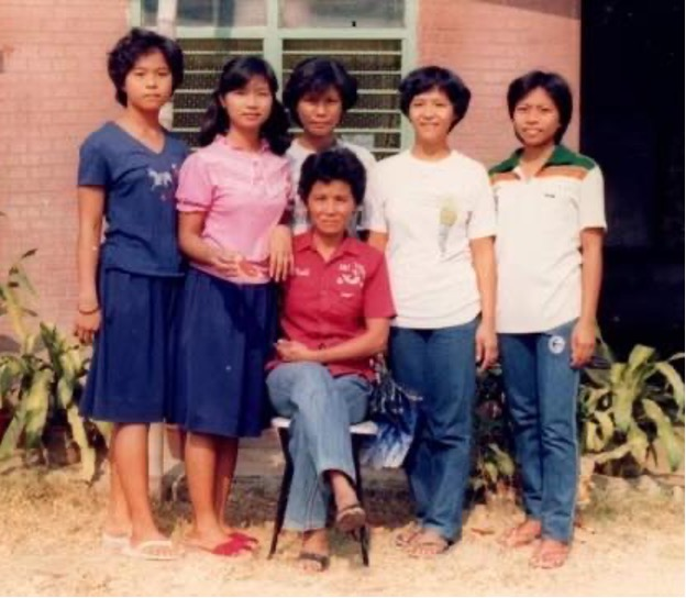 A family posing for a photo outside of their home in Alaminos, Philippines. One person is sitting while five people stand behind them, smiling.