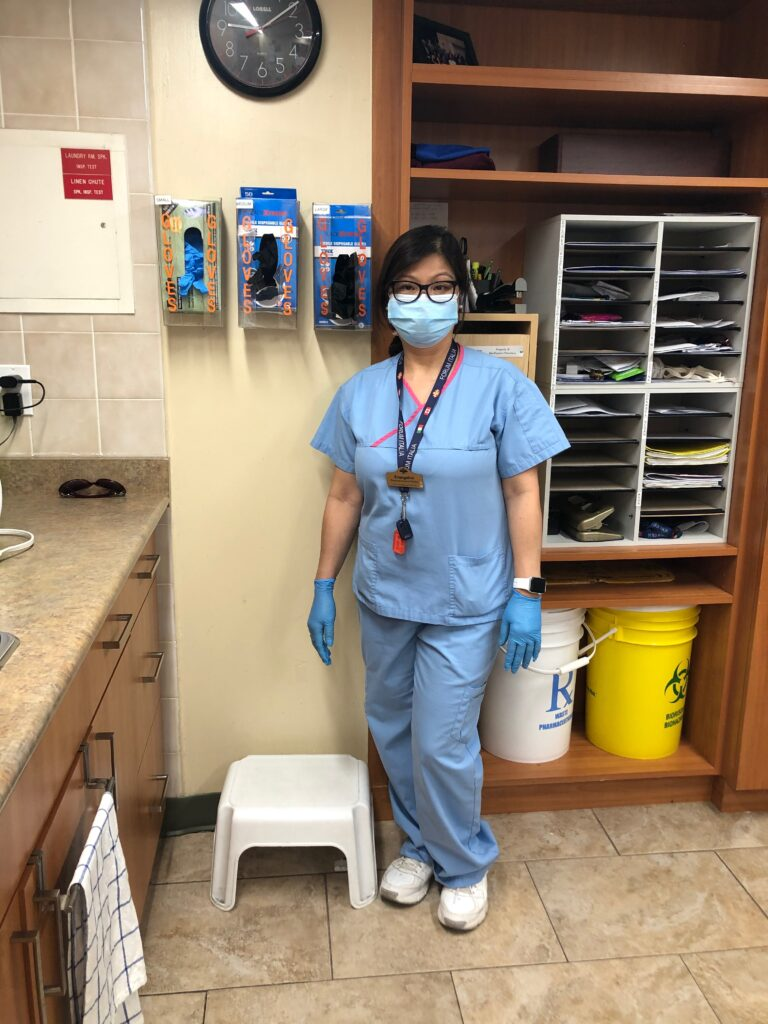 A personal support worker poses for a photo wearing scrubs, a face mask and gloves at a retirement home.