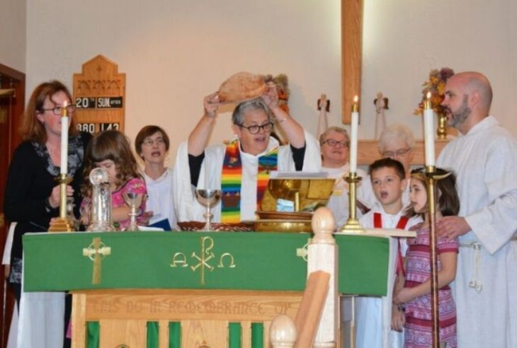 Three young children and a number of adult congregants stand around the altar with Lori Pilatzke, who holds the communion bread.