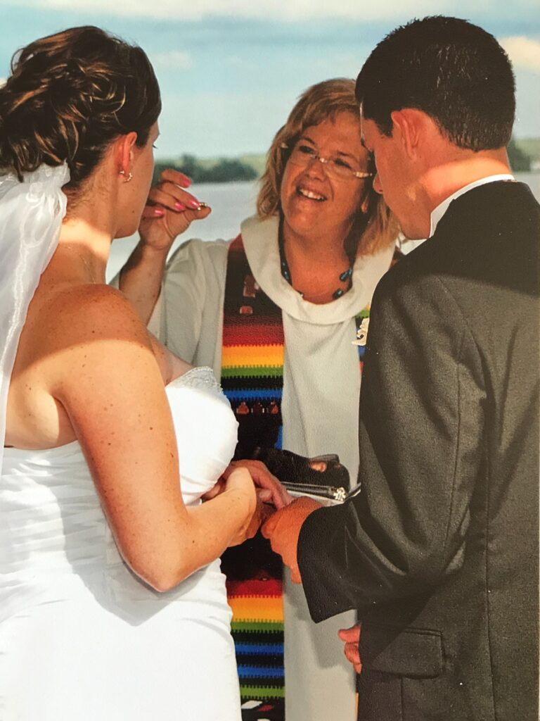 Lori Pilatzke performs a wedding, smiling and holding a wedding ring, as the couple stands in front of her.