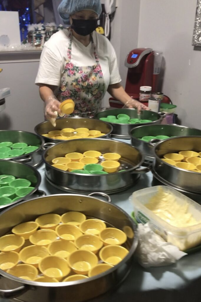 A woman wearing a face mask and hair net arranges small dessert molds into large pans