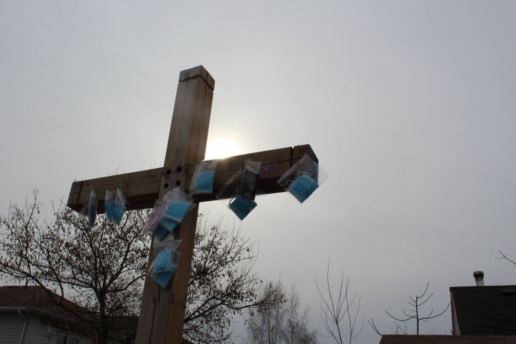 Blue medical masks hang in clear ziplock bags from a wooden cross outside St. David Anglican-Lutheran Church.