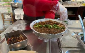A staff member adding fresh cilantro beside the crispy onions.