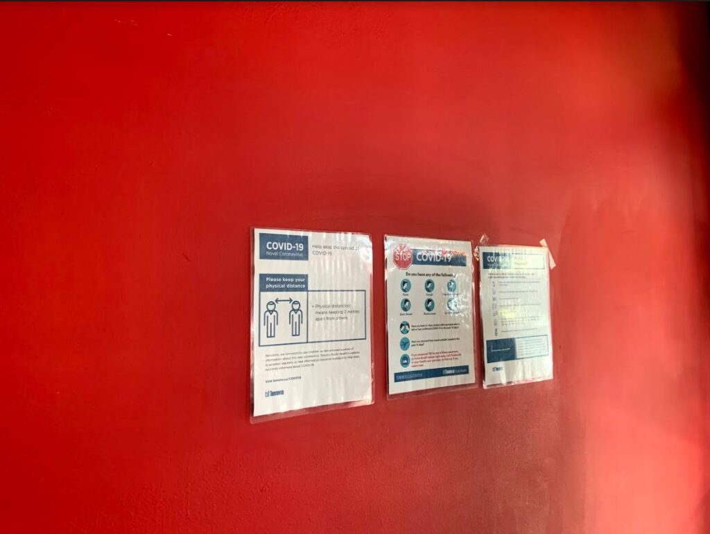 Three signs promoting COVID-19 measures are attached on a red wall.