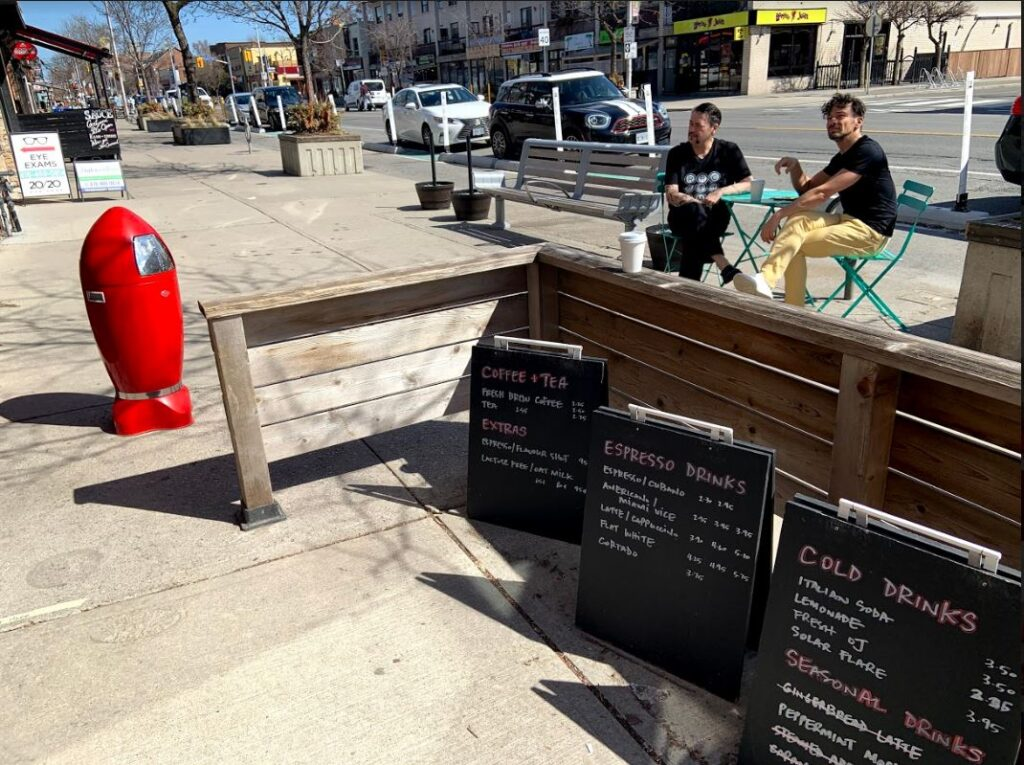 A list of menus written in chalk sit outside Red Rocket Cafe. Behind them, Liako and Billy Dertilis sit on a set of chairs.
