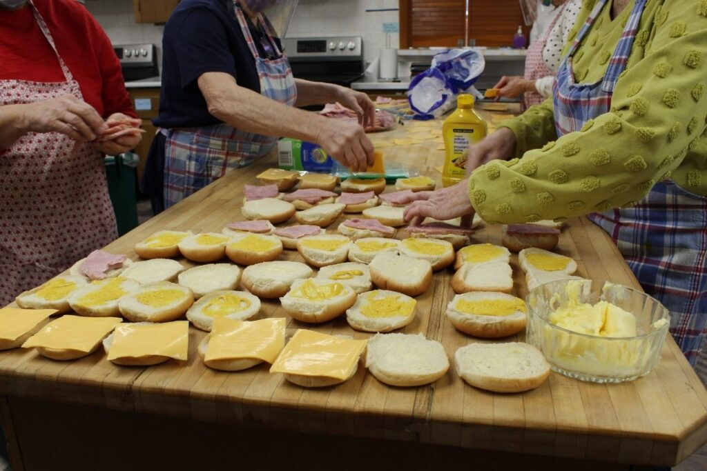 Four women dress sandwiches with cheese, ham, mustard and butter. Rows of open buns lay out on the wooden countertop as the women work.