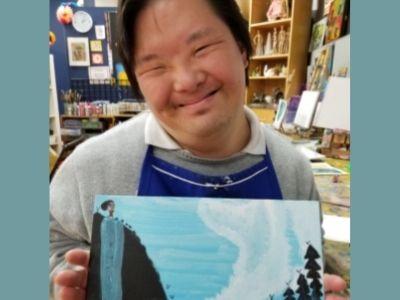 Ixchel Suárez's student poses proudly with painting